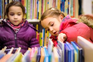 two children looking through books
